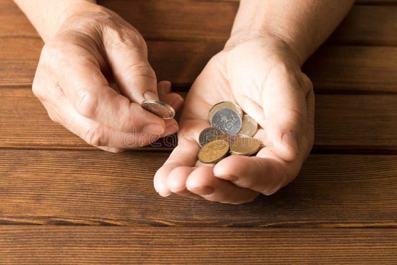 Руки пожилого человека с различными монетками на деревянном столе Th стоковые изображения rf