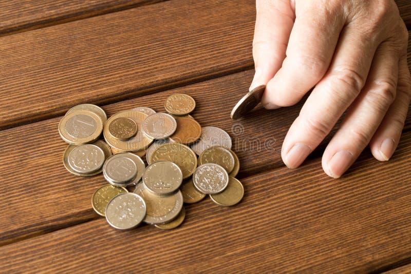 Руки пожилого человека с различными монетками на деревянном столе Th стоковые изображения