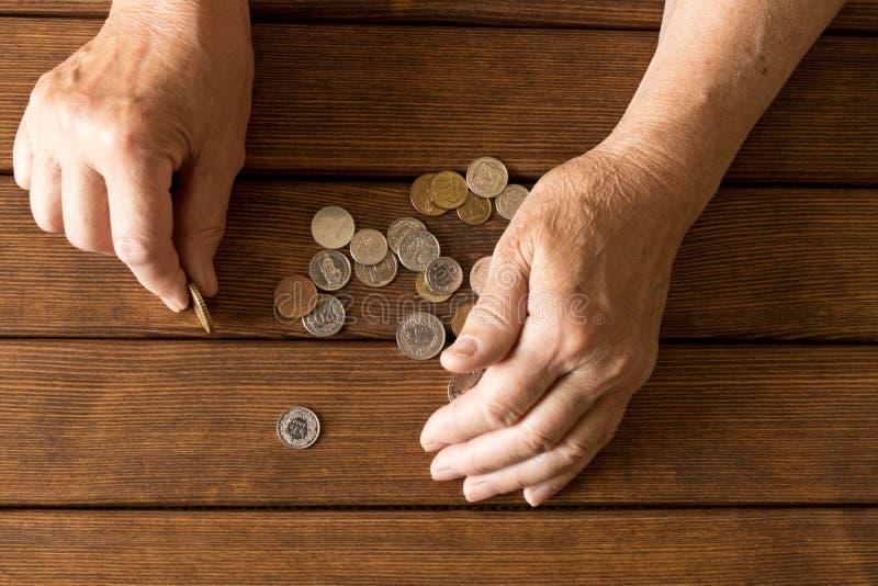 Руки пожилого человека с различными монетками на деревянном столе Th стоковое фото