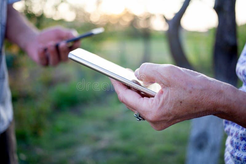 руки пожилых пар, использующих смартфон для передачи данных стоковые изображения
