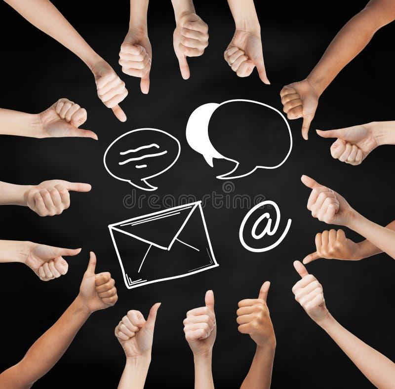 Руки показывая большие пальцы руки вверх с излишек символами электронной почты стоковые изображения rf