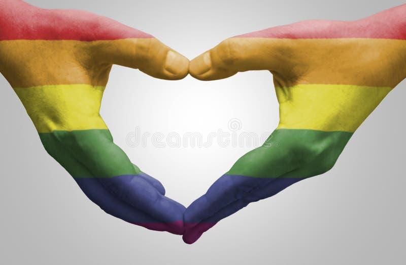 Руки покрашенные как радуга сигнализируют формировать сердце стоковые фотографии rf
