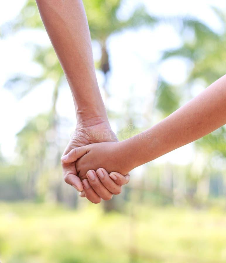 Руки помощи - рука сына отца hoding стоковые фотографии rf