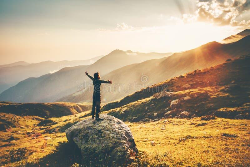 Руки поднятые человеком на горах захода солнца стоковая фотография