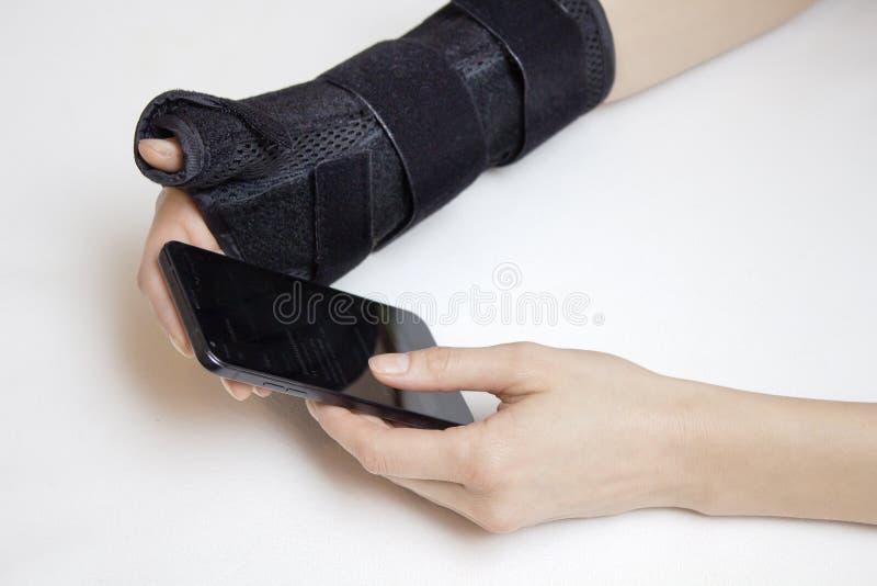 руки предпосылки женские белые Одна рука в стабилизаторе подержанном держит телефон стоковые фотографии rf