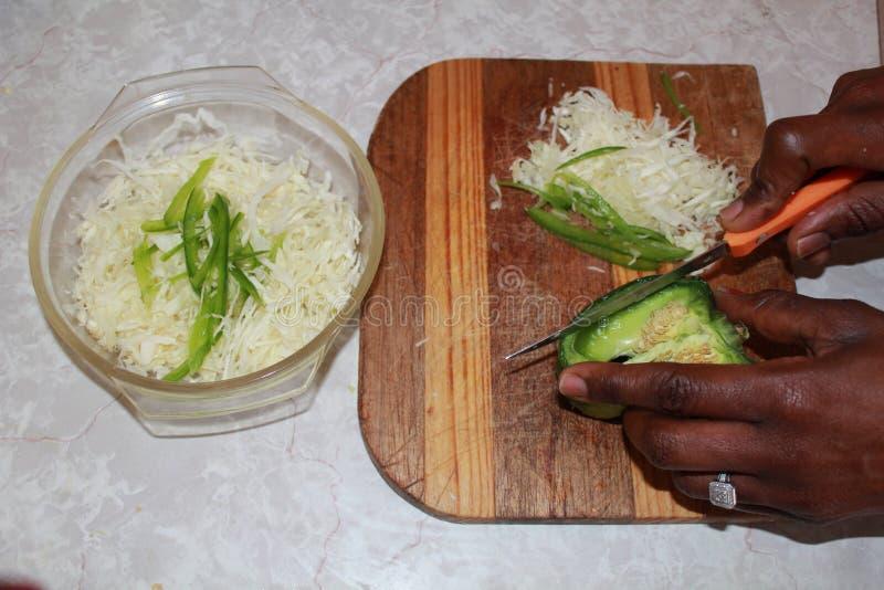 Руки прерывая капусту и зеленый перец стоковое изображение