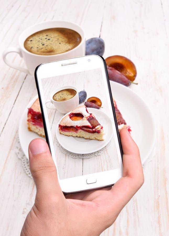 Руки принимая торт сливы фото с smartphone стоковые фото