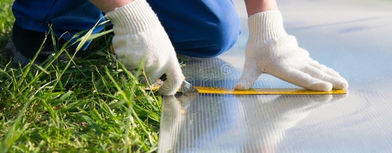Руки профессионального работника в перчатках отрезали с специальным ножом на желтой линии поликарбоната, для установки стоковые изображения rf