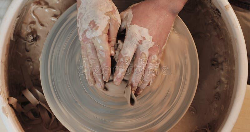 Руки работая на колесе гончарни с профессиональными инструментами, формируя сброс на плите глины r Гончар на работе стоковые изображения rf