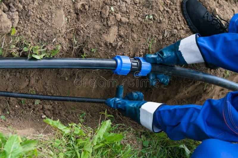 Руки работника держат трубу из черного металла над выкопанным отверстием в земле стоковые фотографии rf