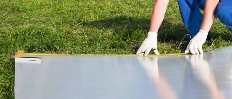 Руки работника измеряют размер с рулеткой, поликарбонат для более дальнеишей установки на парник стоковые фото
