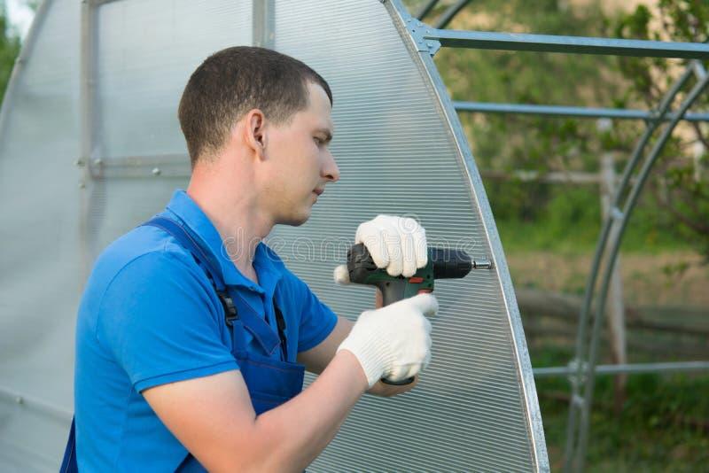 Руки работника переплетают лист поликарбоната с отверткой для установки на парник стоковое изображение