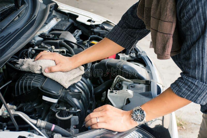 Руки работника человека или автоматического механика очищая двигатель автомобиля с тканью стоковая фотография rf