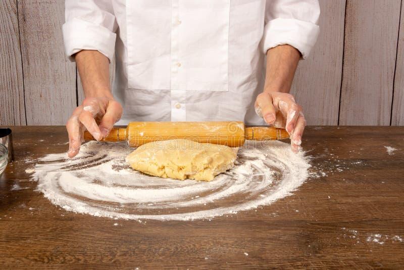 Руки разворачивание тесто с вращающей осью на деревянном столе, в крупном плане кухни стоковое фото rf
