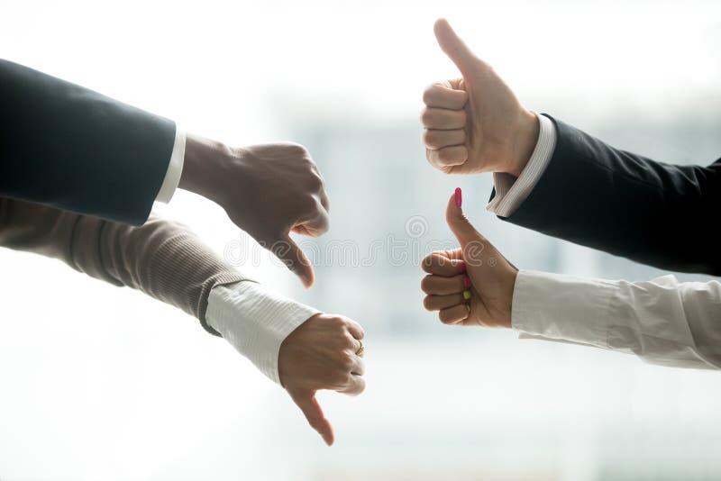 Руки разнообразных бизнесменов показывая большие пальцы руки вверх и вниз стоковые изображения rf