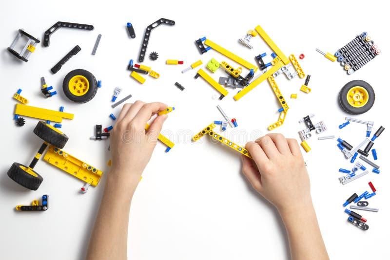 Руки ребенка делая автомобиль робота Робототехнический, учащ, технология, образование стержня для предпосылки детей стоковая фотография rf