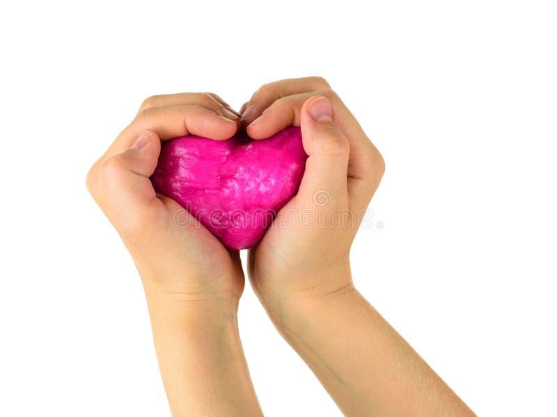 Руки ребенка держат красную игрушку в форме сердца изолированного на белой предпосылке стоковые изображения rf