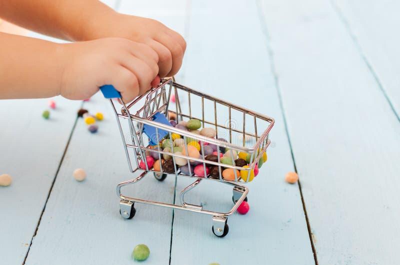 Руки ребенка держа магазинную тележкау с покрашенными помадками на голубой предпосылке стоковое изображение rf