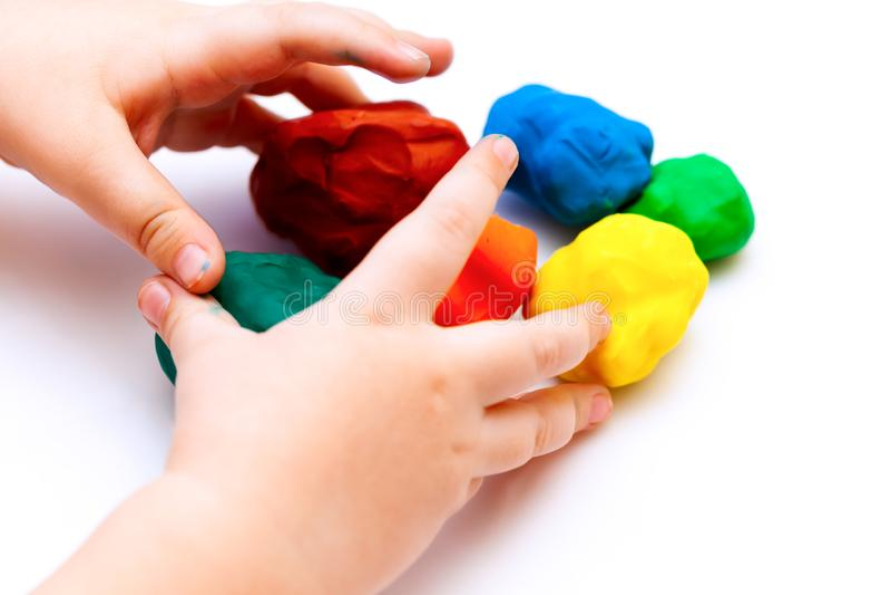 Руки ребенка играя с шариками глины игры стоковая фотография rf
