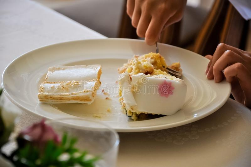 Руки ребенка режа торт с вилкой стоковые фото
