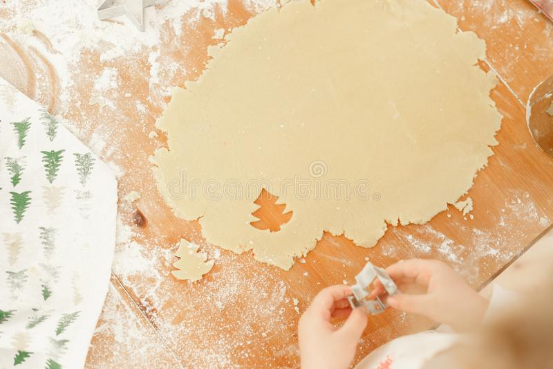 Руки ребенка s делают печенья от теста, резца печенья польз в форме ели, подготавливают на зимние отдыхи, пекут стоковые фото