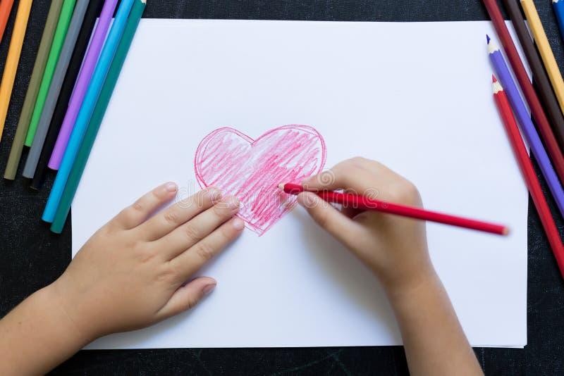 Руки ребенк с карандашем рисуют сердце на белой бумаге Принципиальная схема дня ` s матери Торжество Ручной работы карта Взгляд с стоковое изображение rf