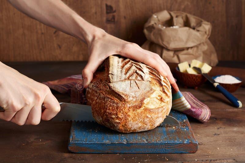 Руки режа хлеб тоста sourdough ремесленника на голубой деревянной доске Простой завтрак стоковое фото