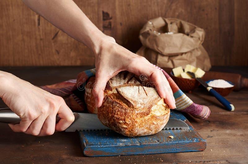 Руки режа хлеб тоста sourdough ремесленника на голубой деревянной доске Простой завтрак стоковая фотография