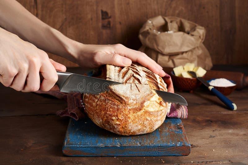 Руки режа хлеб тоста sourdough ремесленника на голубой деревянной доске Простой завтрак стоковые изображения rf