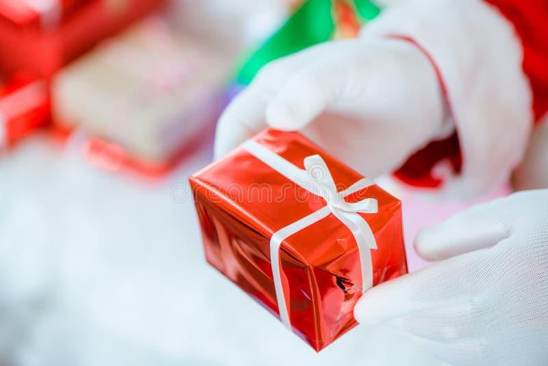 Руки Санта Клауса gloved держа подарочную коробку в комнате Санта Клаус принес подарки для рождества и иметь остатки софой стоковое фото rf
