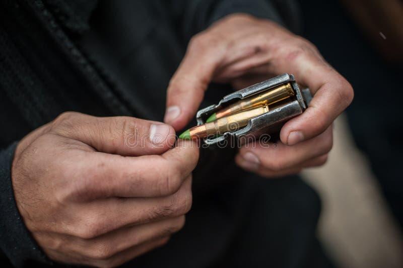 Руки солдата нагружают пули пулемета винтовки в патронную обойму стоковое фото