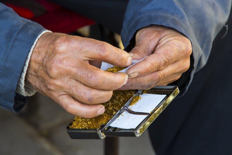 Руки старика переплетают сигареты табака стоковая фотография