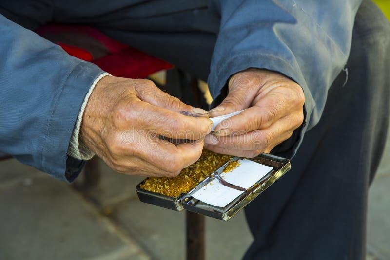 Руки старика переплетают сигареты табака стоковое изображение rf