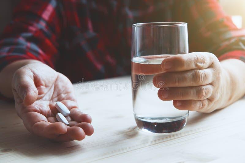 Руки старшей женщины держа стекло воды и таблеток стоковое фото rf