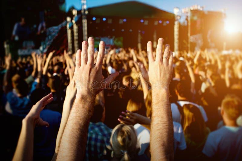 Руки счастливых людей толпятся имеющ потеху на фестивале в реальном маштабе времени утеса лета стоковые изображения rf