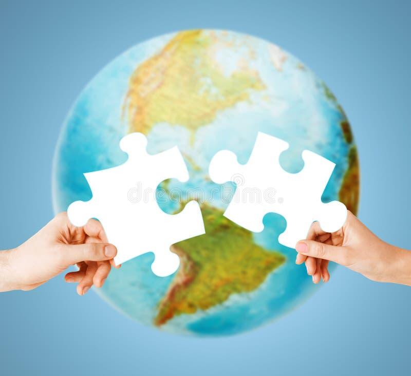 Руки с белой пустой головоломкой над глобусом земли стоковые фотографии rf