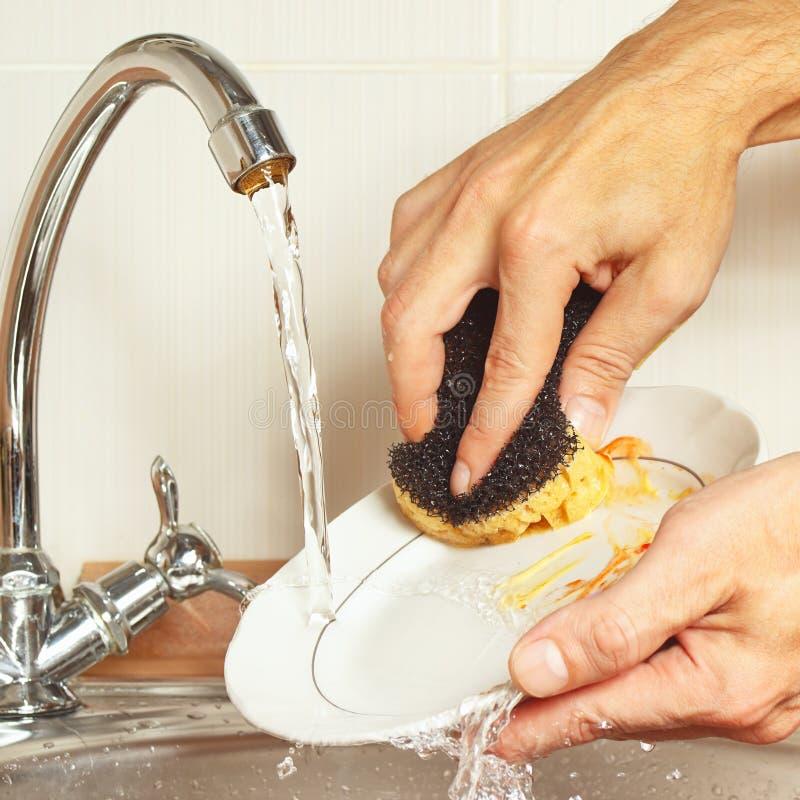 Руки с губкой моют пакостные блюда под проточной водой в кухне стоковое изображение
