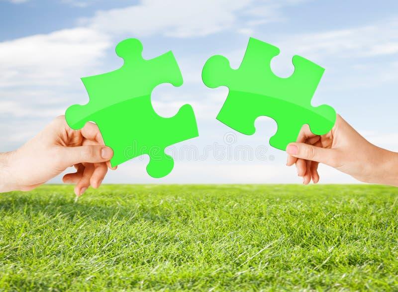 Руки с зеленой головоломкой над естественной предпосылкой стоковая фотография