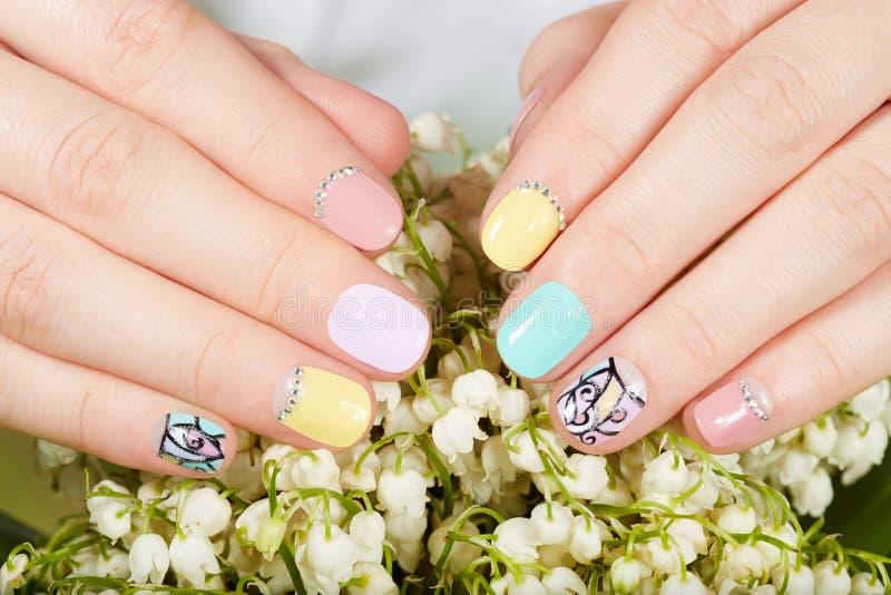 Руки с красивыми деланными маникюр ногтями и цветками ландыша стоковое изображение rf
