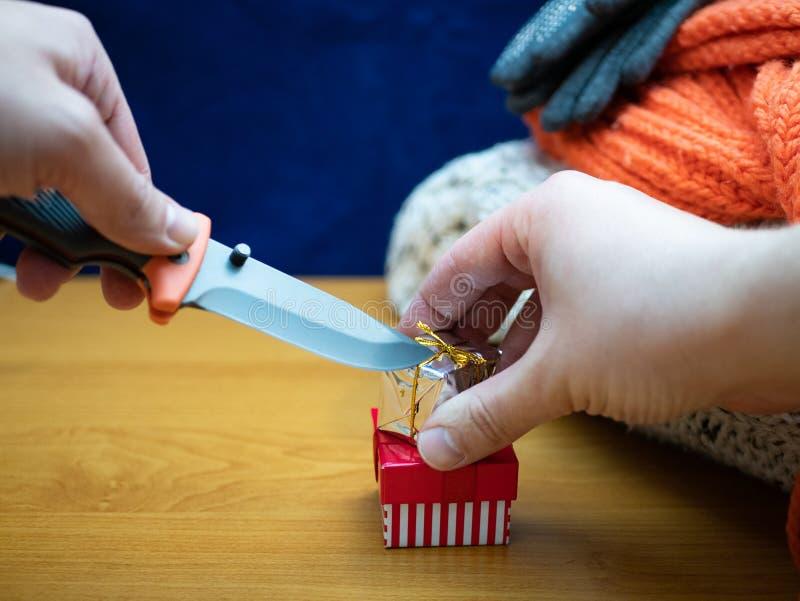 Руки с ножом и небольшим cardbox подарка стоковые фотографии rf