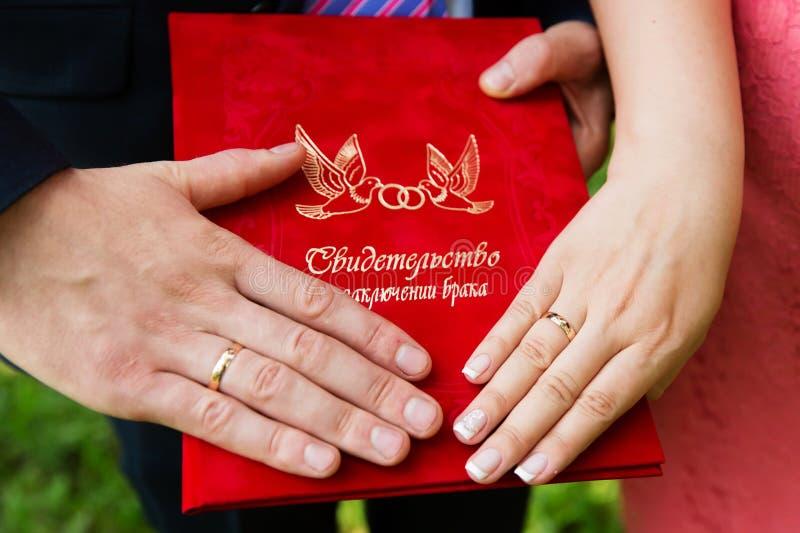 Руки с обручальными кольцами на сертификате замужества стоковое фото rf