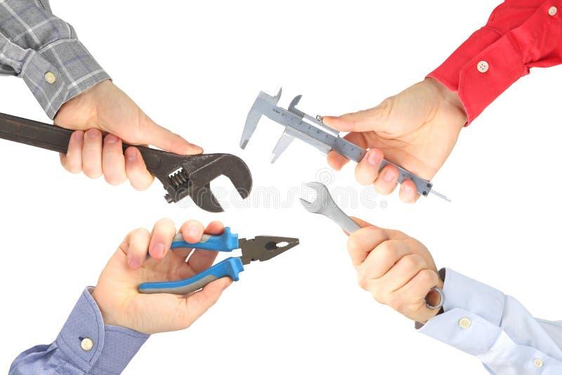 Руки с различными инструментами работы на белой предпосылке стоковые фотографии rf