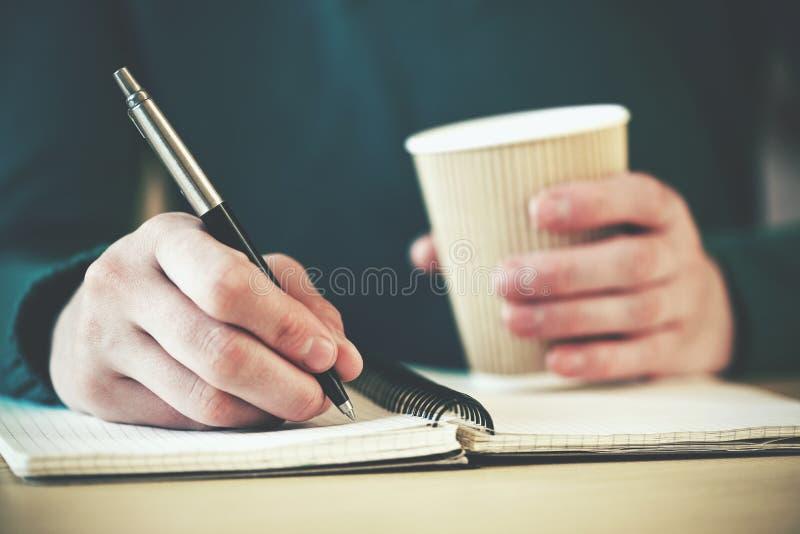 Руки с сочинительством ручки на тетради стоковая фотография rf