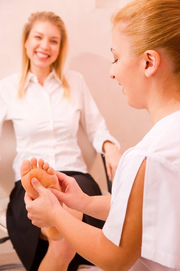 Руки терапевта массажируя женскую ногу стоковые изображения rf
