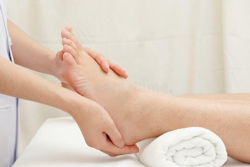 Руки терапевта массажируя женскую ногу стоковое фото