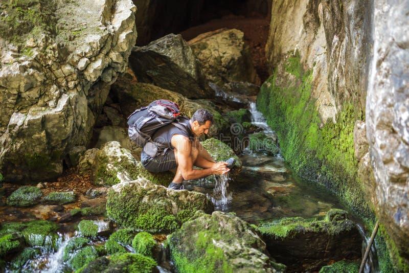 Руки туристского человека моя в реке горы стоковые фото