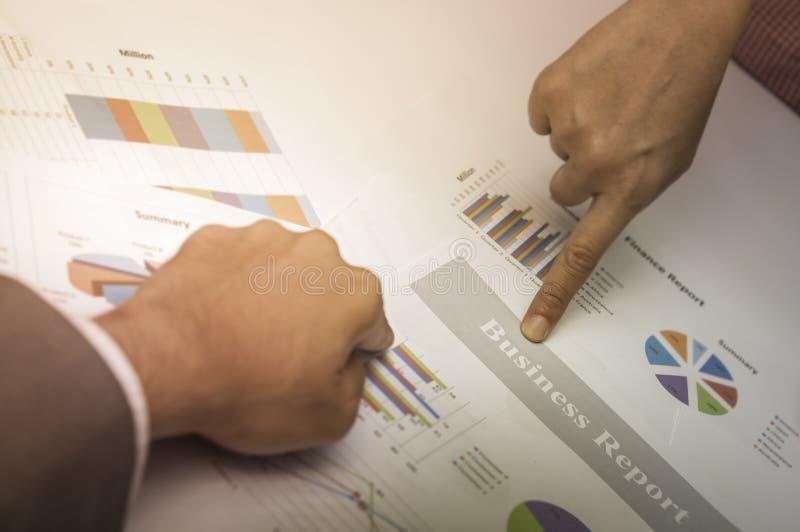 Руки указывают с излишек диаграммой и доходами от бизнеса бизнес-отчета пункта деловых документов стоковое фото