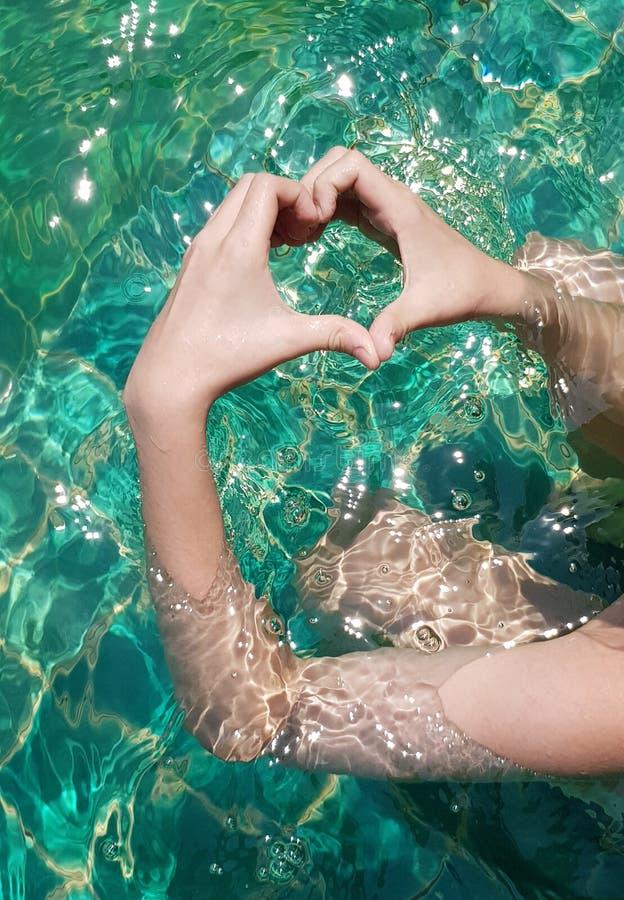 Руки формы сердца в бассейне стоковые изображения rf