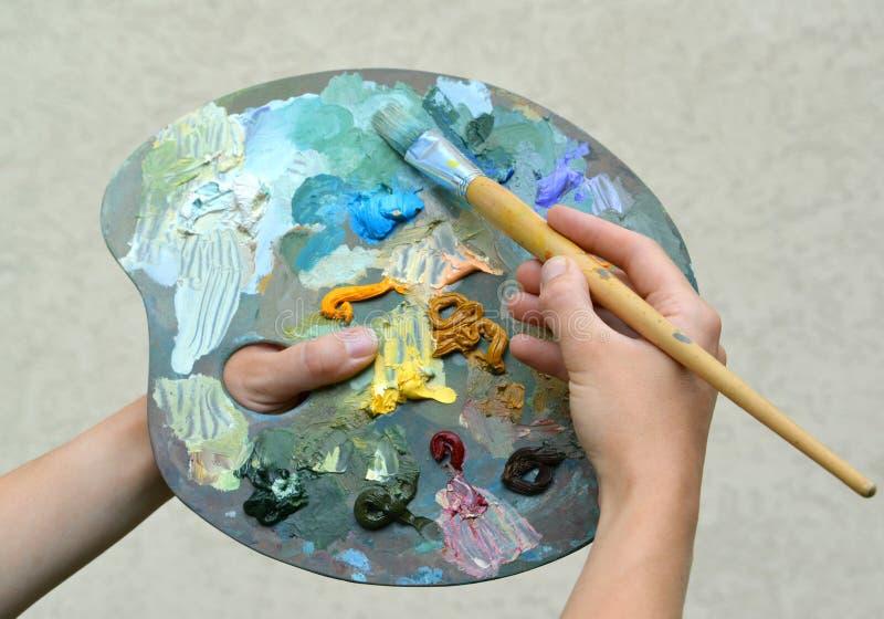Руки художника держат палитру с красками и щеткой стоковые изображения rf