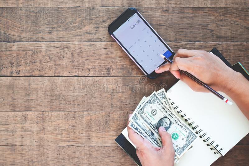 Руки человека взгляда сверху держа счеты доллара США и высчитывая на мобильном телефоне стоковые фотографии rf